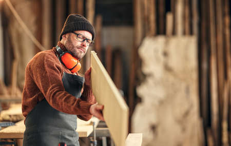 Attentive adult woodworker examining rasped wooden board while working in professional carpentry workshop