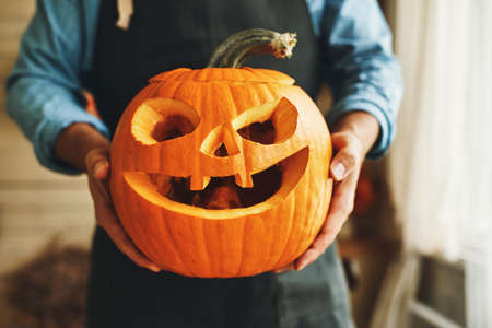 Cropped shot of man in apron with Halloween pumpkin monster in hands, person showing at camera classic carven spooky jack-o-lantern with big, gap-toothed grin, triangular eyes and nose