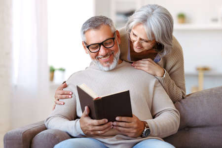 Happy smiling senior family couple in love reading book together, hugging embracing while spending free time at home on retirement, beautiful retired husband and wife enjoying life 写真素材