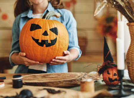 Cropped photo of little kid girl holding classic Jack O Lantern carved orange pumpkin with spooky face during Halloween preparation at home, getting ready for celebration, selective focus 写真素材