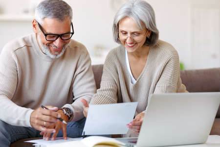 Smiling senior couple calculate expenses or planning budget together, reading notification letter with good news from bank, retired family husband and wife paying bills online on laptop