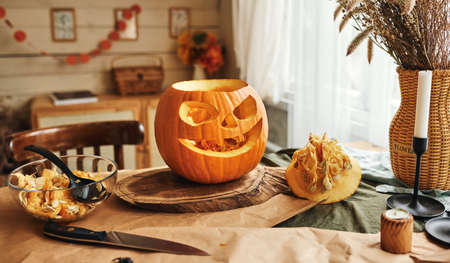 Classic carving spooky jack-o-lantern with big, gape-toothed grin, triangular eyes and nose standing on wooden table in kitchen, selective focus. Halloween pumpkin decorations concept