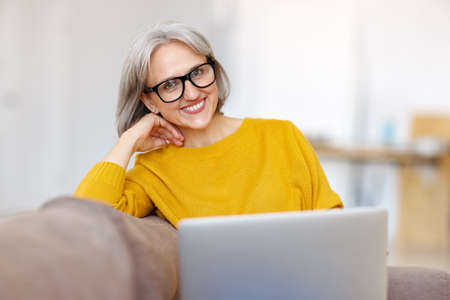 Portrait of happy smiling senior woman resting relaxing on sofa with laptop at home, cheerful retired female doing online shopping browsing internet while enjoying free time on retirement
