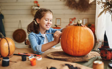 Cute happy little girl preparing for halloween, painting drawing scary face on pumpkin while sitting at table in kitchen at home, smiling child making jack-o-lantern. Holiday decoration concept Фото со стока