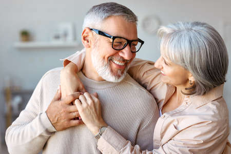 Close up of beautiful smiling senior family couple husband and wife looking at each other with tenderness and love while standing in living room at home, retired man and woman embracing indoors 写真素材
