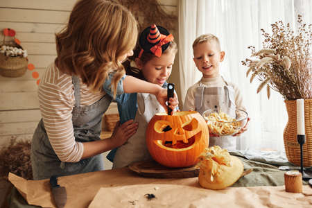 Happy family mother and kids carving pumpkin for Halloween holiday together, preparing for holiday party in kitchen, mom with little daughter and son smiling having fun while creating Jack-o-lantern Фото со стока