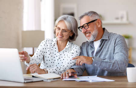 Senior family couple studying online together, retired man and woman looking at laptop and discussing something while sitting at desk at home, enjoying distant education on retirement