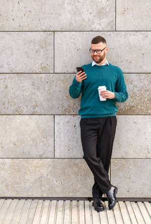 Full length of smiling young office worker in casual clothes standing outdoor with mobile phone, reading last messages from friends during coffee break, employee chatting in social media outside