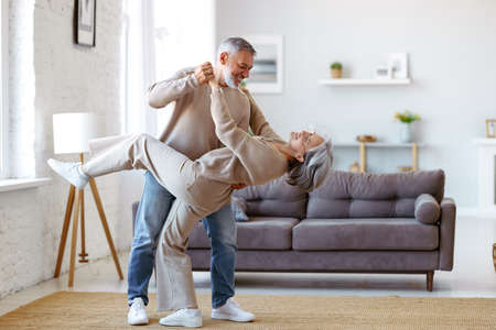 Keep moving. Romantic senior family couple wife and husband dancing to music together in living room, smiling laughing retired man and woman having fun, enjoying free time together at home