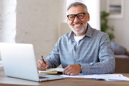 Handsome positive senior man wearing glasses enjoying distant education while sitting at his cozy workplace with laptop computer at home, retired pensioner learning studying online indoors Фото со стока