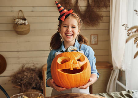 Happy Halloween. Cute cheerful little girl in hat holding carved orange pumpkin with drawn spooky face while standing in cozy rustic kitchen, smiling kid showing classic Jack-o-lantern at camera