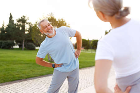 Healthy mind and body. Full length shot of happy smiling mature family man and woman in sportswear stretching arms while warming up together outdoors in park on sunny morning. Active lifestyle Фото со стока