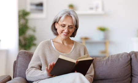 Beautiful happy senior woman with gray hair in eyeglasses reading book and smiling while resting on sofa in living room at home, pleasant retired female enjoying interesting life on retirement Фото со стока