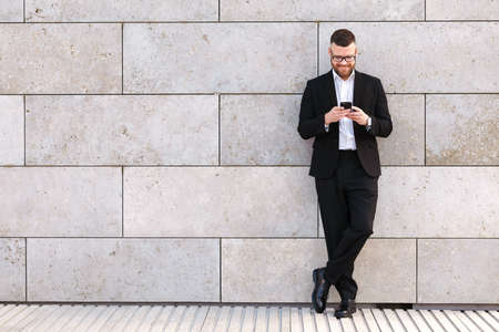 Full length of smiling young office worker in formal suit standing outdoor with mobile phone in hands, reading last emails or messages, chatting with friends in social media during work break Фото со стока