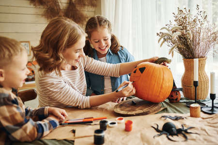 Positive young family mother with children son and daughter smiling while creating jack-o-lantern during Halloween celebration, happy mom and kids drawing on pumpkin in kitchen at home