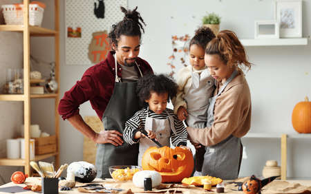 Big happy ethnic family parents with two kids preparing for Halloween celebration while sitting together at table in kitchen, smiling children making Jack-o-lanterns together with father and mother