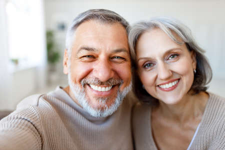 Portrait of happy beautiful senior caucasian family couple smiling at camera, cheerful retired wife and husband making selfie on smartphone while spending time together at home Фото со стока