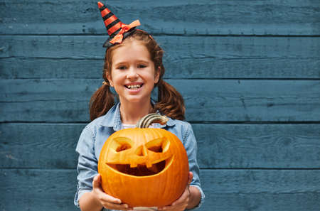 Happy smiling little girl holding Halloween pumpkin monster in hands and looking at camera while standing against wooden wall, cute kid in witch hat with scoopy jack-o-lantern outdoors