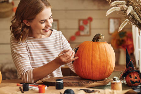 Young woman drawing scary face on orange pumpkin with paint brush for house decoration during Halloween holiday, female creating jack-o-lantern while sitting at table in kitchen at home