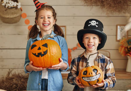Cute happy children sister and brother holding carved orange pumpkins with drawn funny faces while preparing for family Halloween party at home, kids showing Jack-o-lanterns at camera
