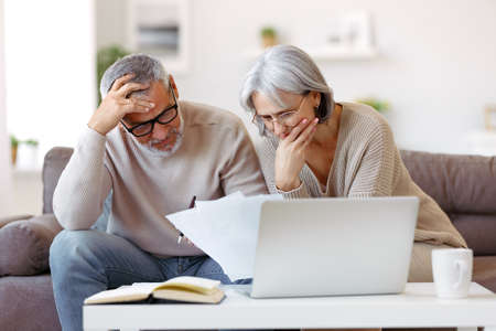Worried senior family couple reading financial documents or notification letter with bad news from bank while paying bills online on laptop, retired husband and wife having money problems