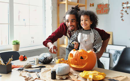 Smiling african american parent father removing pulp from ripe pumpkin while carving jack o lantern with little son for Halloween celebration at home in kitchen and looking with smile