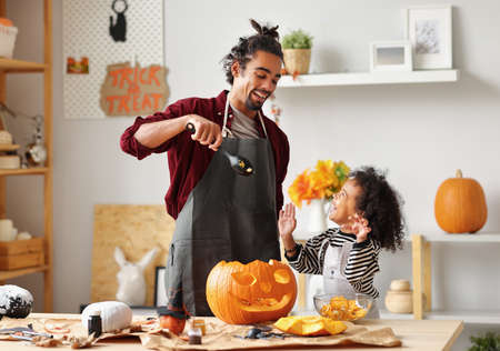 Smiling african american parent father removing pulp from ripe pumpkin while carving jack o lantern with little son for Halloween celebration at home in kitchen and looking at each other with smile