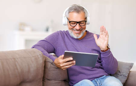 Handsome happy senior man waving by hand while talking online on digital tablet with family, retired pensioner enjoying video call with friends while sitting on sofa at home, smiling at webcam