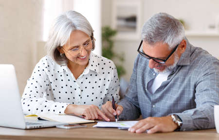 Senior happy family couple doing homework together while studying online on laptop at home, retired man and woman using laptop computer, learning foreign language on retirement