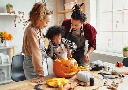 Happy ethnic family mother, father and son carving pumpkin for Halloween holiday together, preparing for holiday party in kitchen, having fun while creating Jack-o-lantern