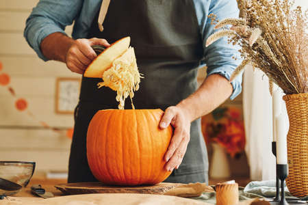 Cropped shot of man standing in kitchen and scooping out removing all the pulp from large orange pumpkin while creating classic traditional jack-o-lantern for Halloween home decoration