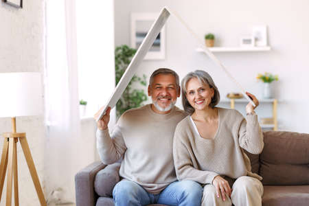 Portrait of happy beautiful senior caucasian family couple holding white roof above head symbol of new home while sitting on sofa, smiling retired husband and wife relocating moving in big dream house 写真素材