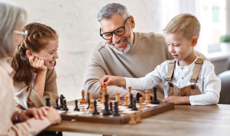 Joyful children brother and sister playing chess while sitting in living room with senior grandparents while spending time together on weekend, kids sitting at table with chessboard and smiling