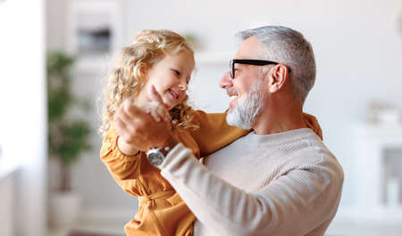 Elegant loving caring grandfather looking at his cute little granddaughter, adorable child girl and positive grandpa holding hands while dancing together in living room at home. Family concept