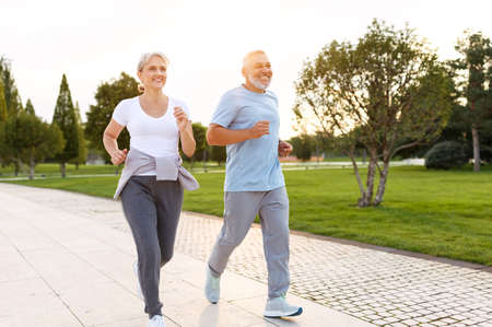 Full-length photo of happy senior husband and wife in sportive outfits running outdoors in city park, lovely retirees couple jogging in sunny morning. Healthy lifestyle concept