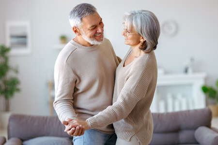 Beautiful senior couple in love looking at each other with tenderness while dancing together in living room at home, two pensioners wife and husband enjoying happy life moments on retirement