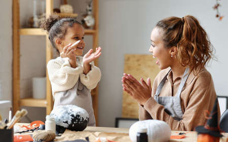 Happy ethnic family mother and little kid daughter making jack-o-lanterns together while preparing for halloween party, sitting in cozy kitchen at home, smiling mom and child girl paint on pumpkins