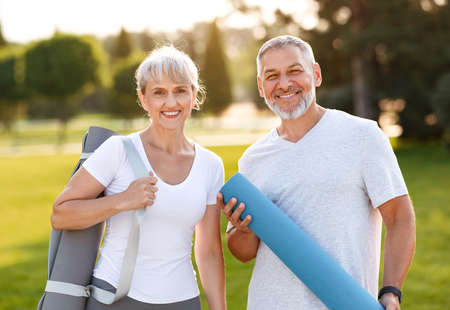 Smiling senior couple with exercise mats standing at park, positive mature man embracing his elderly wife after fitness or yoga class in nature. Wellness and healthy lifestyle on retirement 写真素材