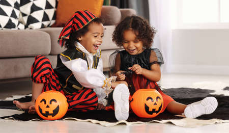 Two cute african kids brother and sister in Halloween costumes playing with artificial spider toy while sitting on floor with orange pumpkin lantern during All Saints Day Party at home