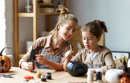 Happy smiling family mother and daughter making Halloween home decorations together while sitting at wooden table, mom and little girl painting pumpkins and making paper cuttings
