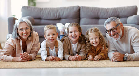 Beautiful cheerful family three cute little kids lying on floor with positive senior grandparents while playing together in living room at home, happy children enjoying time with grandma and grandpa