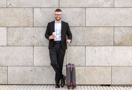 Ready for business trip. Full length of young happy stylish businessman in formal outfit with suitcase luggage standing against concrete wall outside and smiling, holding take away coffee in hand