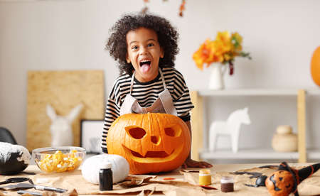 Playful little afro american boy holding carved orange pumpkin and sticking out tongue while standing behind table with Halloween decorations, smiling kid showing Jack o lantern with spooky face at camera
