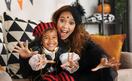 Joyful african american family mother and little boy son in Halloween costumes making scary gesture and looking at camera while sitting on sofa in decorated living room, celebrating all hallows day