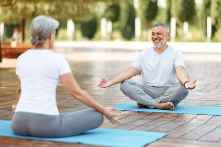 Happy positive mature man sitting in yoga lotus pose with hands in mudra gesture and smiling during morning meditation practice with wife on fresh air in park, senior family couple meditating outdoors