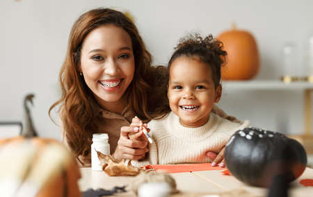 Beautiful happy afro american family mother and cute little girl painting Halloween pumpkins together at home, mom and kid sitting at table and preparing handmade decorations for all hallows day 写真素材