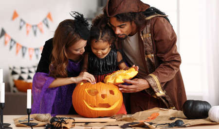 Young african american family in Halloween costumes mother father and cute little girl daughter making together jack o lantern from pumpkin, parents with kid preparing for celebration at home