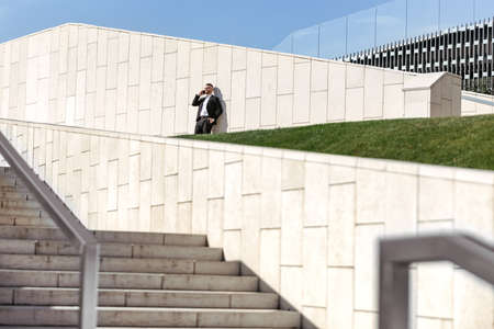 Young satisfied businessman in formal suit speaking on mobile phone smartphone while standing on concrete stairs outside during coffee break at work, office worker enjoying sunny day outside