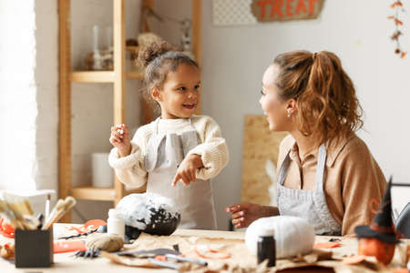 Cute little african american girl holding paintbrush and painting Halloween pumpkin with mom together at home, loving parent and kid sitting at table and preparing handmade decorations for Saints Day party 写真素材