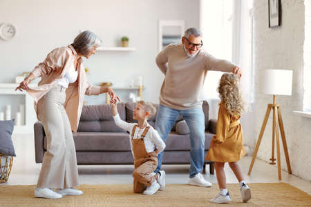 Active senior grandparents dancing with two happy kids grandchildren in living room, small children sister and brother having fun in living room while playing with grand mother and grandfather